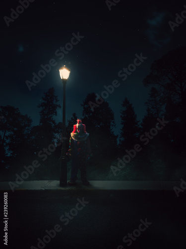 Fotografia dramatic lit image of a clown besides a lamp post at night