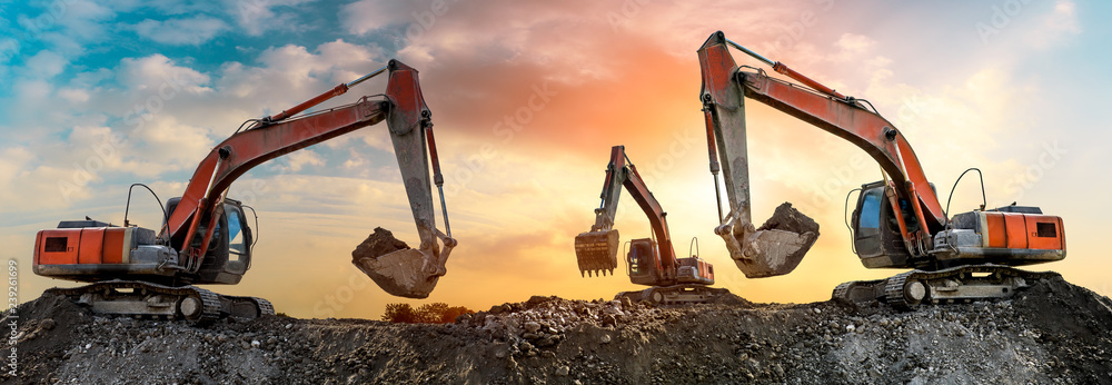 Fotografía  Three excavators work on construction site at sunset,panoramic view