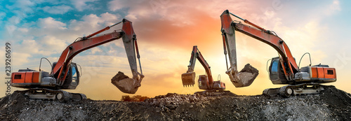 Photo  Three excavators work on construction site at sunset,panoramic view