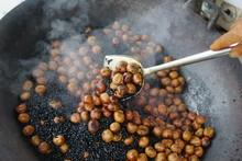 Smokey Roasting Brown Chestnuts In A Big Pot. Street Food Market.