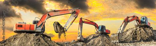Fotomural Three excavators work on construction site at sunset,panoramic view