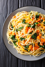 Organic Spaghetti Meal With Pumpkin, Spinach And Cheddar Cheese Close-up On A Plate. Vertical Top View
