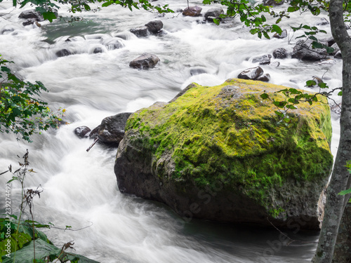 Photo  Giant rock with green moss in fast flowing river at Ryu Sei waterfall, Hokkaido, Japan