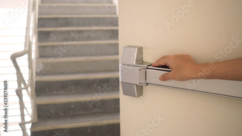 Fotografia Hand is pushing Fire door handle of Fire exit for emergency evacuation