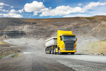 Modern Yellow Truck With White Heavy Duty Dump Trailer Drives After Load From Quarry In A Sunny Day
