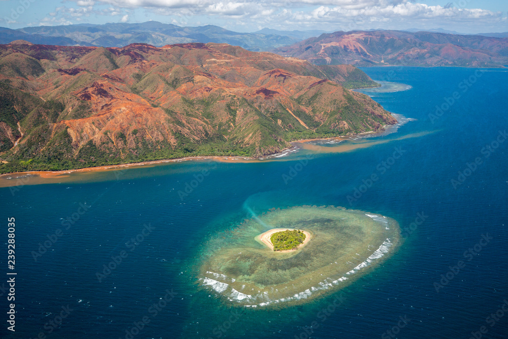 Fototapeta A small atoll islet with heart shaped coral reef off the east coast of Grande Terre island of New Caledonia, French overseas collectivity. Red green mountains hills full of nickel ore near Nakety.