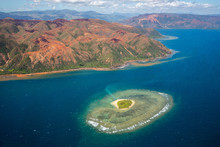 A Small Atoll Islet With Heart Shaped Coral Reef Off The East Coast Of Grande Terre Island Of New Caledonia, French Overseas Collectivity. Red Green Mountains Hills Full Of Nickel Ore Near Nakety.