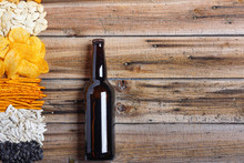 Chips, Crackers, Seeds, Nuts And Bottle Of Fresh Cold Beer On Wooden Table