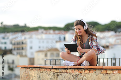 Happy teen watching and listening video on a tablet