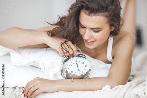 Obraz Attractive young woman awake in the morning. Beautiful girl in the bed after sleep. Female holding alarm clock indoors. - fototapety do salonu