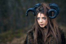 Outdoor Portrait Of Beautiful Young Woman Warrior With Blue Eyes And Specific Makeup Wearing Ram Horns And Fur Collar