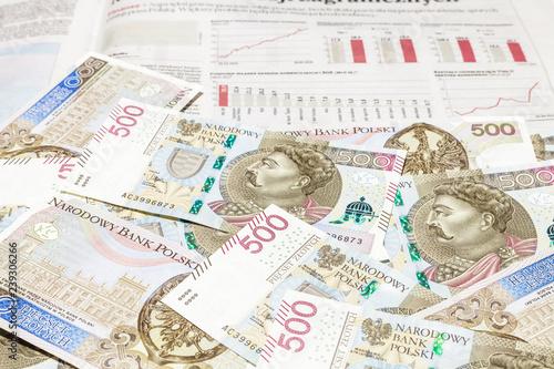 Plik banknotów 500 PLN na tle wykresów i słupków