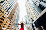 Young pretty woman in red dress and straw hat walking beetween skycrapers in modern city. Low angle view