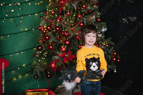 Fotografie, Obraz  Little happy cute boy near the Christmas tree and holds a gift box