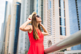 Young pretty woman holding straw hat wearing in red dress and sunglasses in front of skycrapers.