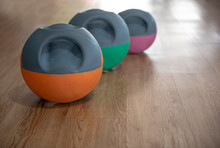 Colorful Kettlebells In A Row On Wooden Floor In A Gym,  Orange, Green, Pink