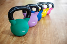 Colorful Kettlebells In A Row On Floor In A Gym, Green, Violet, Blue,yellow, Pink.