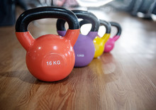 Colorful Kettlebells In A Row On Floor In A Gym, Orange, Violet, Yellow, Pink.