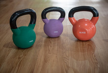 Colorful Kettlebells In A Row On Floor In A Gym, Green, Violet, Orange,