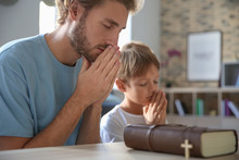 Father With Son Praying At Home