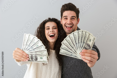 Fotografie, Obraz  Image of rich man and woman holding fan of dollar money, isolated over gray back