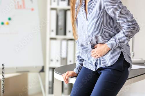 Stampa su Tela  Young woman suffering from abdominal pain in office