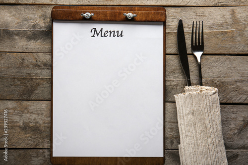 Blank menu with cutlery on wooden table