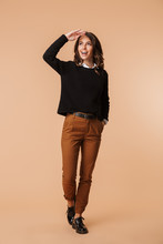 Full Length Of A Cheerful Young Woman Wearing Sweater