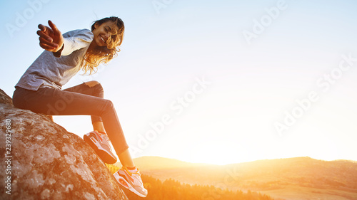 smiling woman hiker sits on edge of cliff against background of sunrise