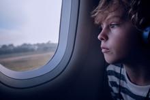 Cute Boy With Headphones In Plane