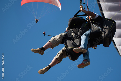 Keuken foto achterwand Luchtsport Two paraglider tandem fly against the blue sky,tandem paragliding guided by a pilot