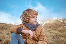 Cute Boy Sitting On Hill Near Brook