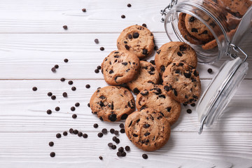 Tasty cookies with chocolate chips and overturned jar on white wooden table