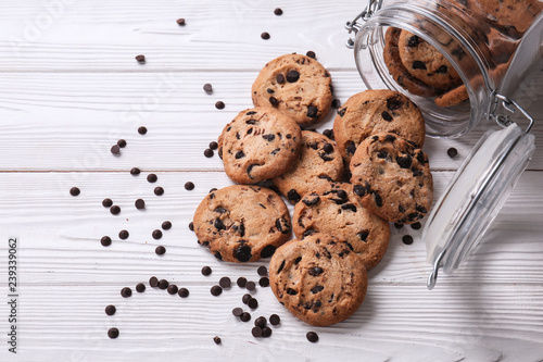 Tasty cookies with chocolate chips and overturned jar on white wooden table Fotobehang