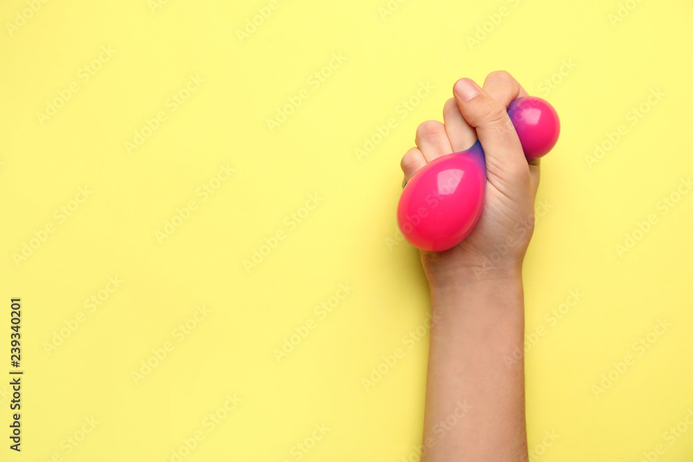 Fototapety, obrazy: Female hand squeezing stress ball on color background