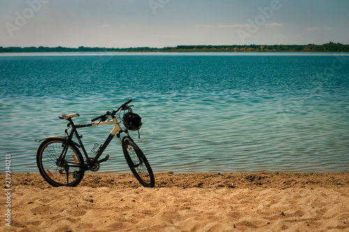 Foto op Plexiglas Sports bike with a helmet on the steering wheel stands on a yellow sandy beach on the shore of a beautiful blue pond.