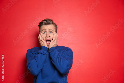 Fotografía  Portrait of scared young man on color background