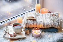 Beautiful Autumn Composition With Burning Candles And Cup Of Tea On Window Sill