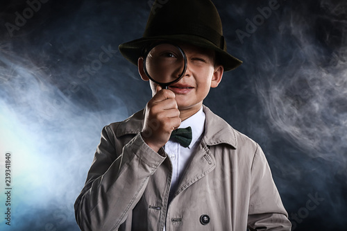 Fotografia Cute little detective with magnifying glass in smoke on dark background