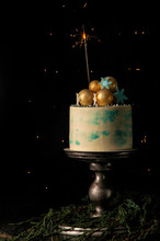 Close Up. Christmas Cake And One Burning Sparkler Festively Decorate It. Dark Background With Christmas Lights.