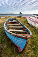 View Towards Lindisfarne Castle With An Old Blue And Red Fishing Boat In The Foreground, Lindisfarne (Holy Island), Northumberland, England, United Kingdom, Europe