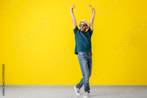 Handsome young man dancing near color wall