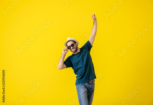Handsome young man dancing on color background