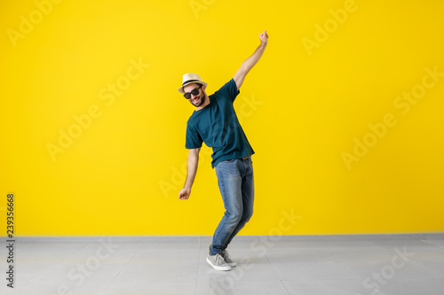 Handsome young man dancing near color wall - 239356668