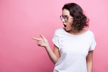 Good Looking Young Caucasian Woman In Round Transparent Eyewear, Keeps Hand Raised, Dressed In Casual Outfit, Pretends Holding Something Wonderful, Isolated Over Pink Background. Look There