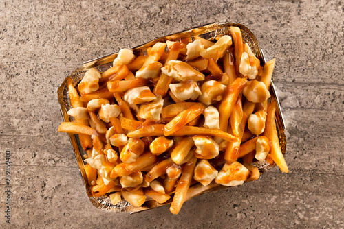 Poutine in a takeout container. Cooked with french fries, beef gravy and curd cheese. Canadian cuisine.