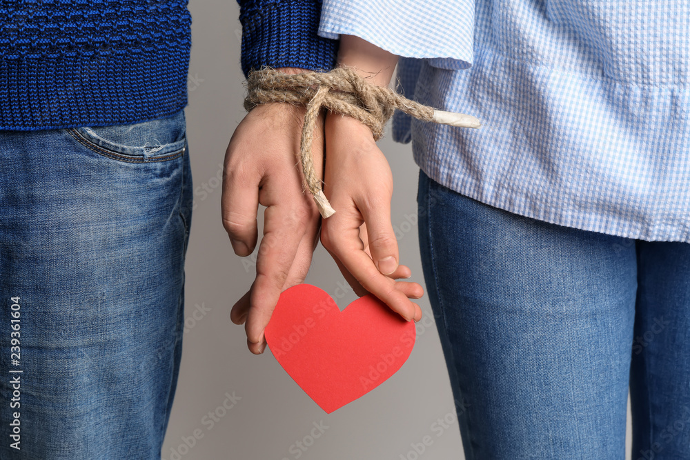 Fototapeta Couple with tied together hands holding paper heart on light background. Concept of addiction