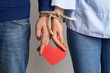 Couple with tied together hands holding paper heart on light background. Concept of addiction