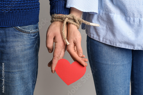 Fotografia  Couple with tied together hands holding paper heart on light background