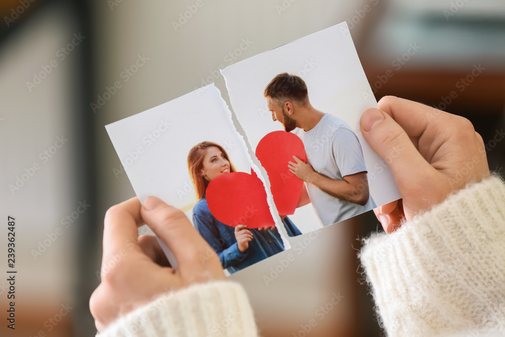 Fototapety, obrazy: Woman tearing up photo of happy couple, closeup. Concept of divorce